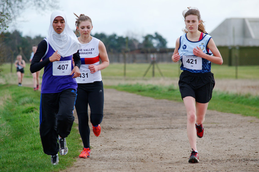 Three young females running in a cross country race