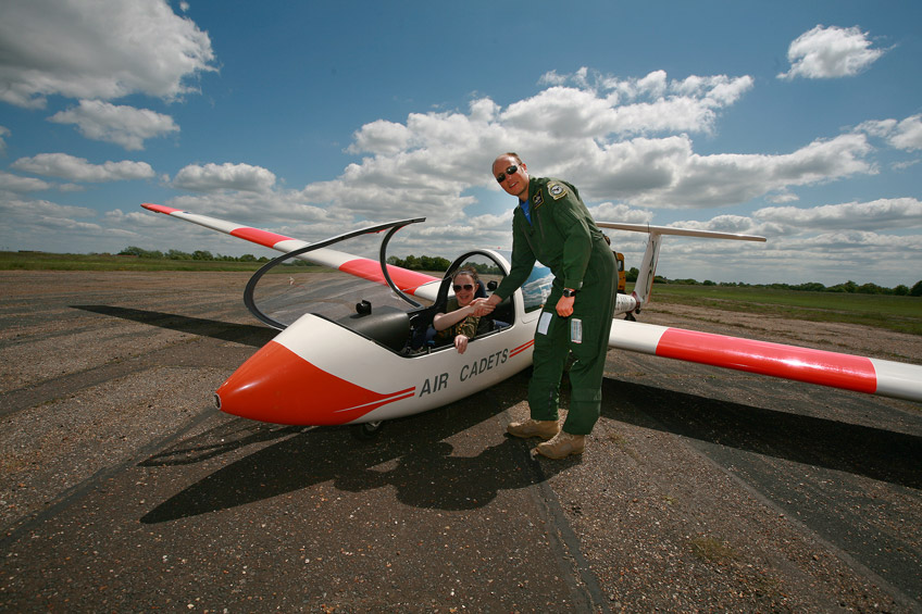 A Gliding instructor congratulating a female cadet after a successful solo flight