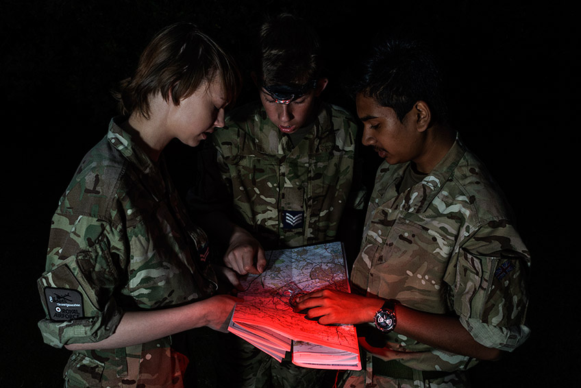 Three young male cadets map reading with a compass at night