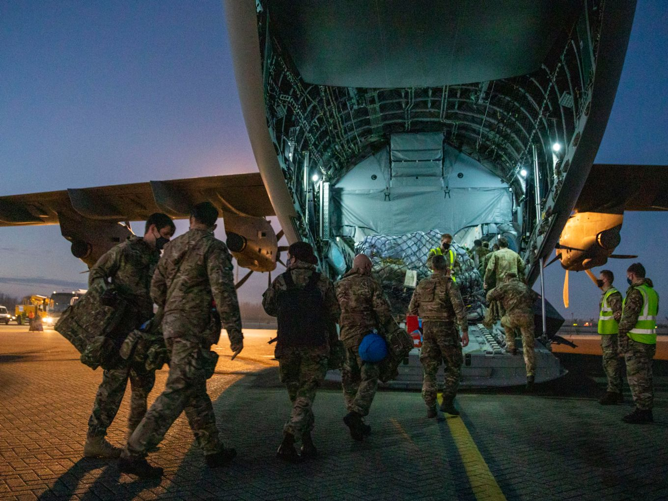 Image shows military personnel boarding an RAF A400M aircraft from the rear.