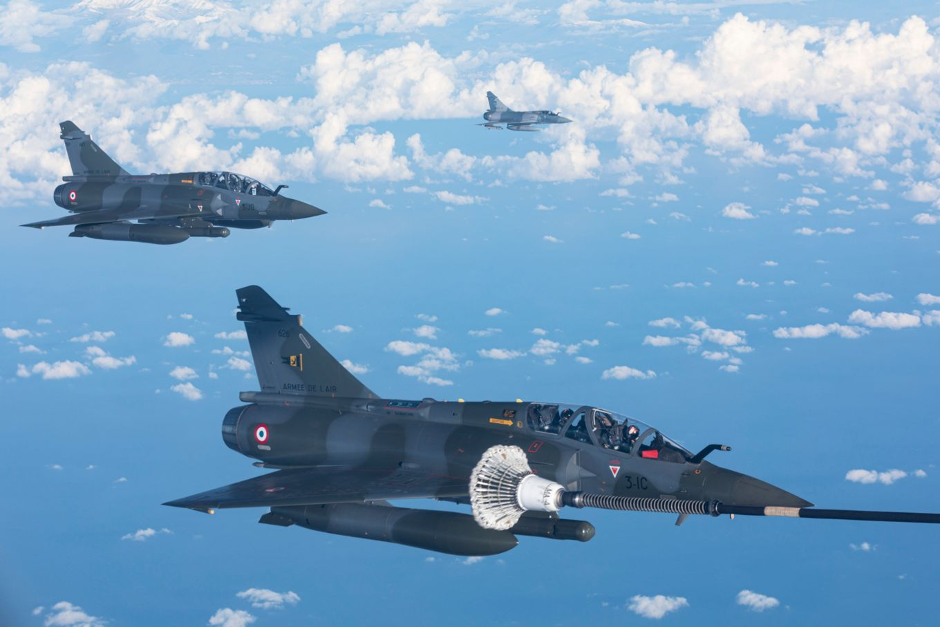 Image shows three French Mirage 2000 aircraft flying.