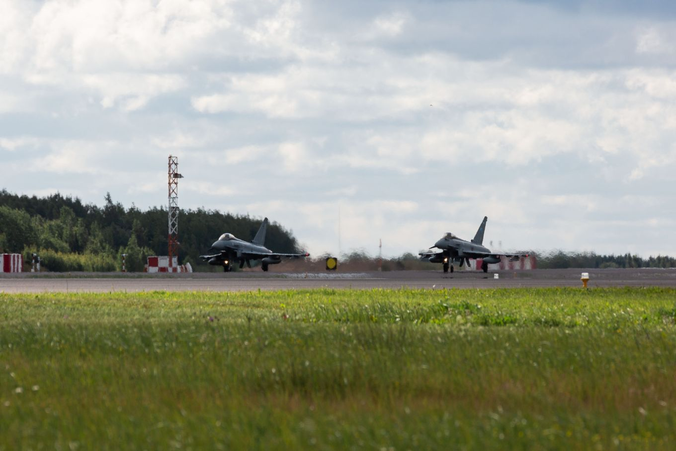 Image shows an RAF Typhoon and a German Eurofighter taxiing on the runway.