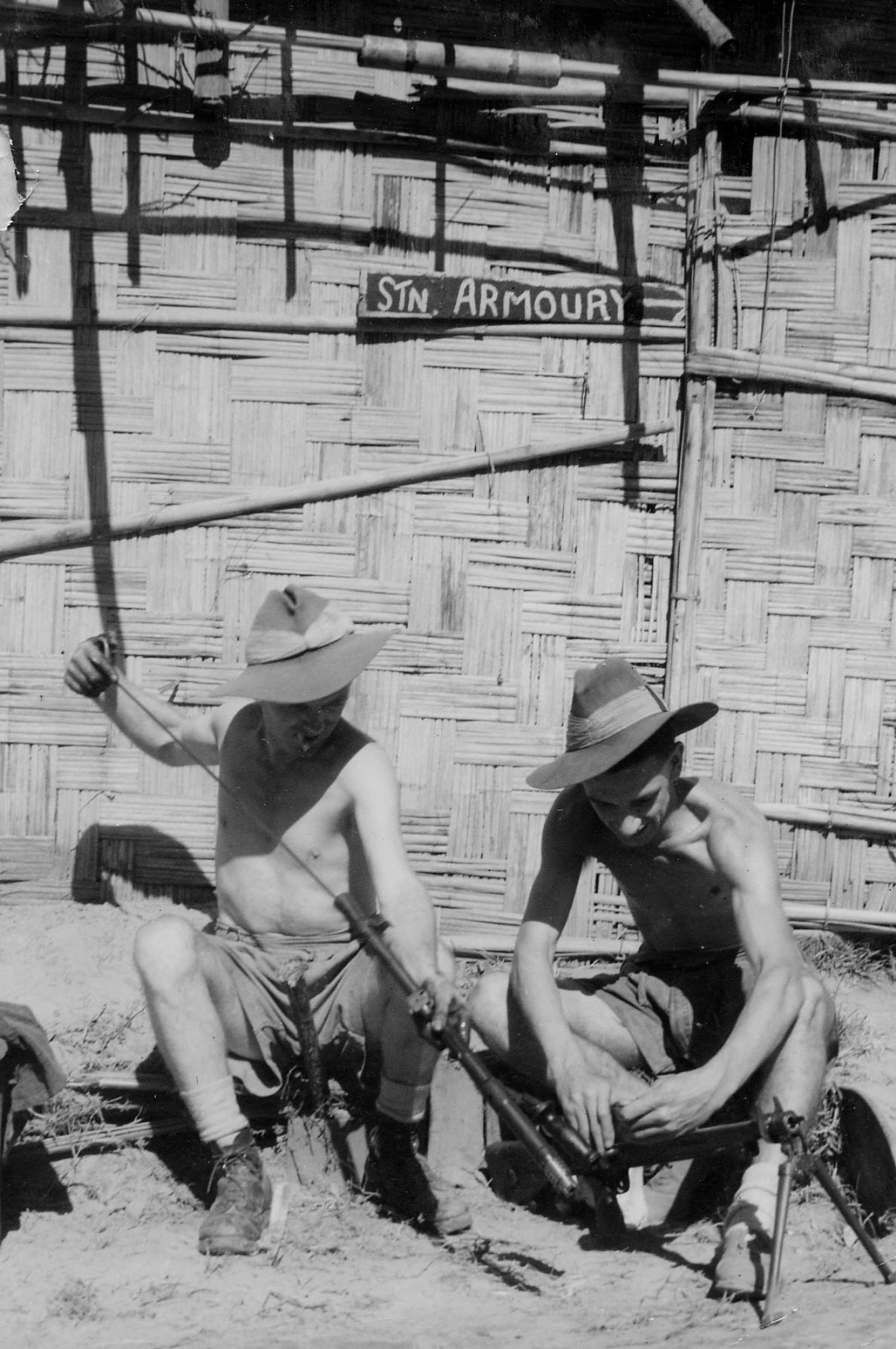 Two airmen of the RAF Regiment cleaning and oiling a Bren gun outside the Armoury of their camp at Maungdaw, Burma
