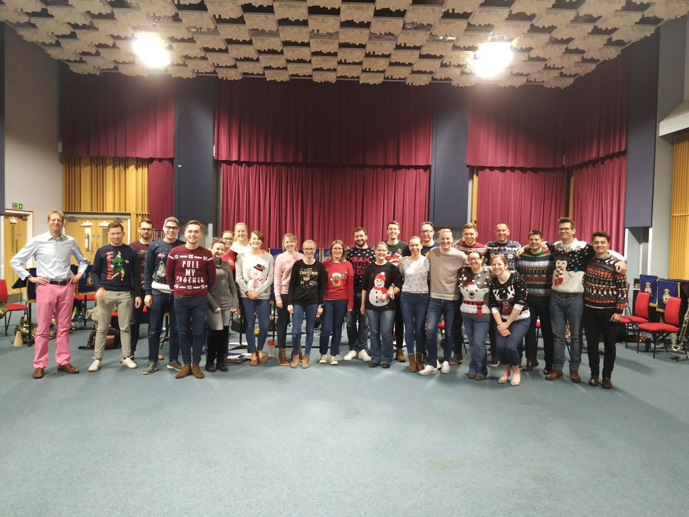 People in Christmas jumpers pose for a picture.