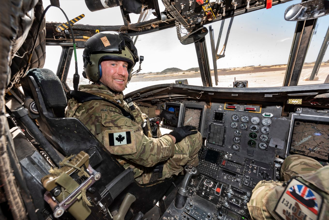 Image shows Captain Stewart in the cockpit of a Chinook helicopter.